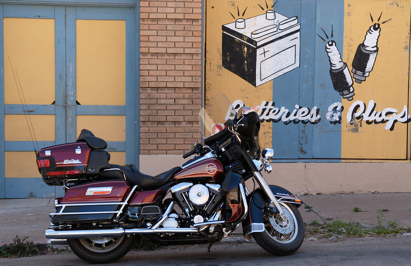 Harley-Davidson on sidewalk in front of abandoned car shop in a modern ghost town outside Bisbee, Arizona.
