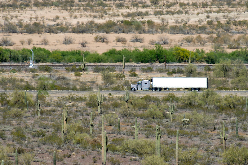 Semi-truck traveling thru shimmering waves of heat in the Arizona desert.