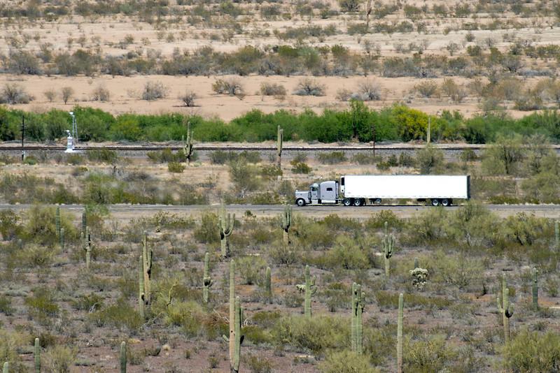 Semi-truck traveling thru shimmering waves of heat in the Arizona desert.