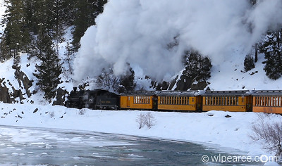 The Polar Express chugging along the river on a sweeping turn.