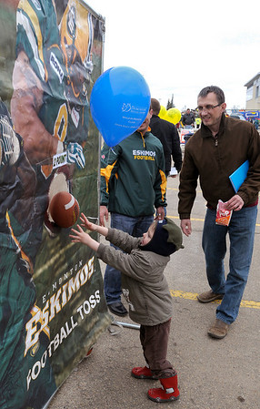 Father and son enjoy the Eskimos' Football Toss during the carnival at Century Park.