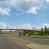 This rendering shows the Connors Road Pedestrian Bridge from a reverse angle. The LRT train below it has recently left the Muttart stop.