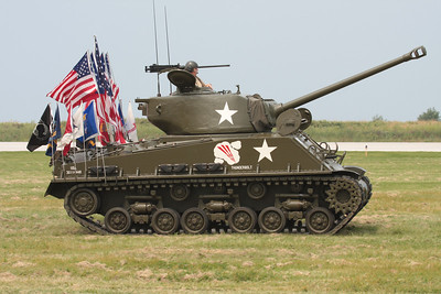 A restored WWII Sherman tank with various flags on the rear