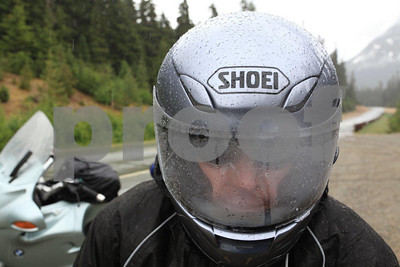A rider stops on Rainiy Pass during a rain storm to put on rain gear while traveling the North Cascdes Highway.