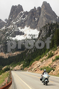 A biker on a BMW R1100RT heading east on the North Cascades Highway with Liberty Bell in the bakcground, Washington State.