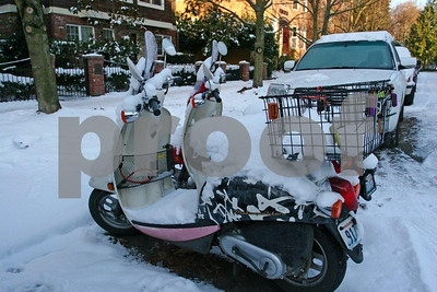 Two motor scooters snowbound in Seattle, WA.