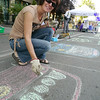 Sidewalk chalk artist drawing parked - car free day logo's on road.