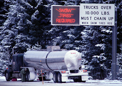 Semi-trucks chaining up for winter drive over Snoqualmie Pass on I-90 in Washington State.