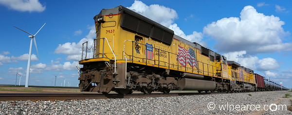 UP 3937 pushes a mile long oil train through a wind farm in central Texas.  A contrast of old and new.