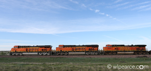 BNSF triple lash-up express headed northwest about 60 miles south of Amarillo, TX.  Two southbound coal trains were on separate sidings waiting for the speed demon to make it through.