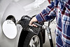 Mans Hand holding Gas Nozzle to Refuel Vehicle