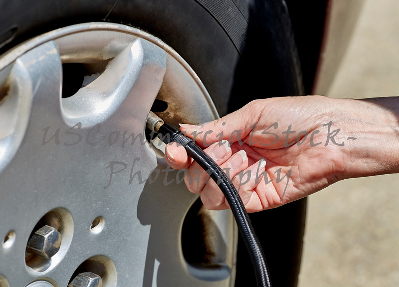 Womans hand putting air in car tire