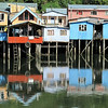 """ Palafitos ""  By  Anne Macdonald.<br /> <br /> A wonderful array of colour reinforced by the reflections in the water. The stilts act well to keep the dwellings dry. Do you think the bike gets much work?	13"