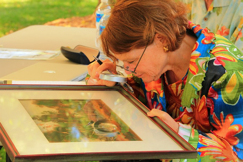 Expert Susanne Milner studies artwork.