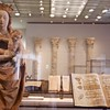 A statue of Mary, next to illuminated ancient texts.