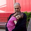 Makeda nestles into her father's arms at the playground on the NYU/AD campus.
