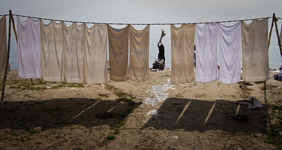 A woman washes clothes on the banks of the Ganges River in Varanasi, India.