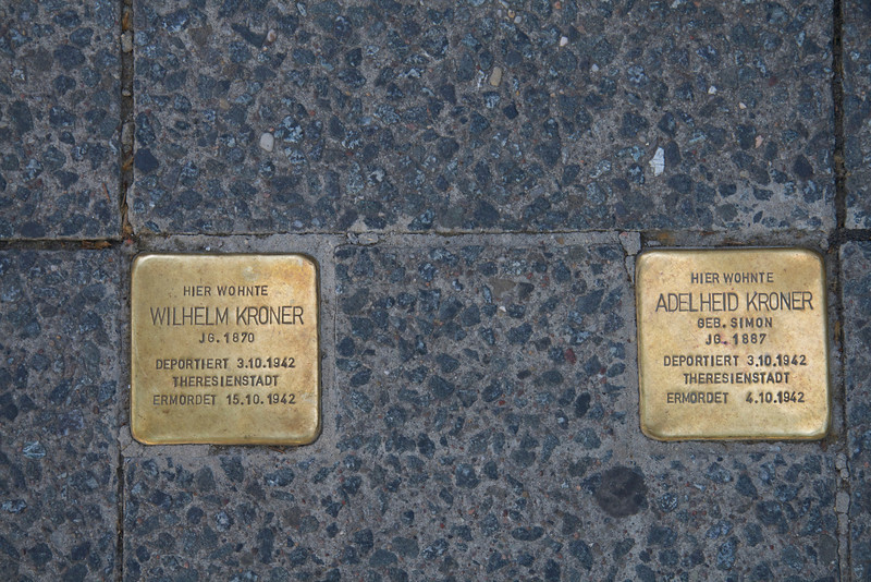 """Two """"Stolpersteine"""" (literally, """"stumbling stones"""") commemorating places where people were arrested and deported to death camps in World War II.  There are thousands of these on Berlin sidewalks today."""