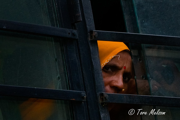 Old woman looking through bus window in Agra,  India