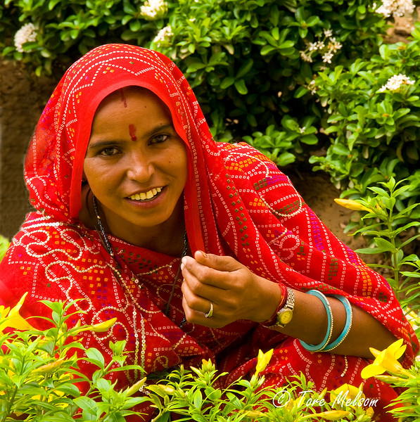 Woman in flower bed, Amber Fort, Jaipur, India