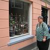 Window art in Groningen - an iron grate with jade trees growing into it, decorated with fairy lights and silk flowers. Pamela is looking worried about the camera flash.