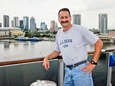 Scott on upper deck of Carnival Legend with Tampa in background.