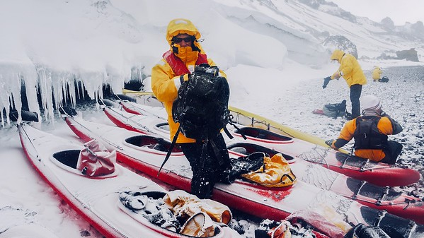Extreme weather conditions in Antarctica as snow falls on sea kayaks, men and gear on an icy beach on the Antarctic peninsula. Brown Bluff, Antarctica.