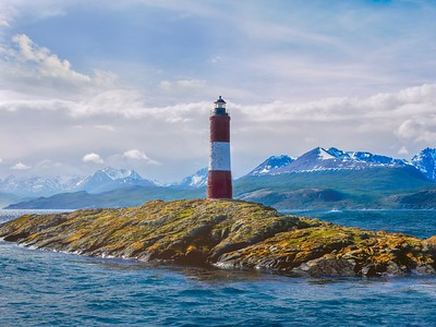 the picturesque Les Eclaireurs (the scouts) Lighthouse on a small island in the Beagle Channel in Tierra del Fuego, Argentina, with the snowcapped Andes mountains in the background