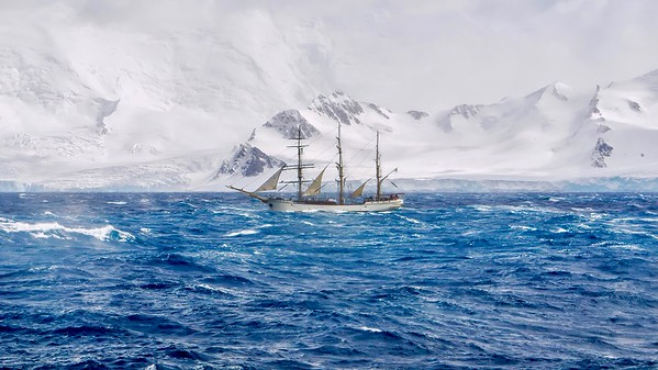 Extreme sailing conditions in Antarctica, as a three masted schooner sails south in a gale, passing the snow-capped mountains and glaciers of the South Shetland Islands.