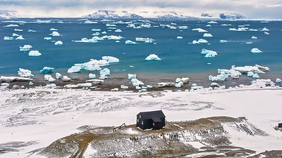 High angle landscape view taken on Snow Hill Island, Antarctica, showing the black Swedish Nordenskjold Hut, Admiralty Sound dotted with icebergs, and James Ross Island in the distance.