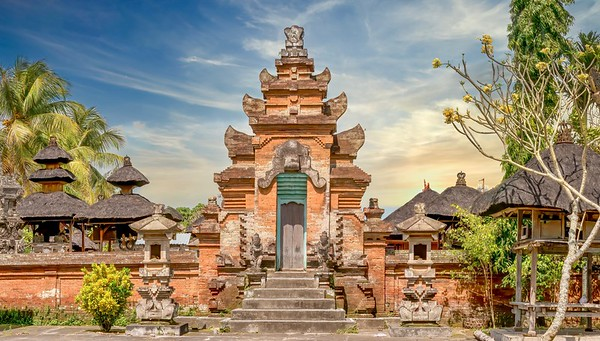 Street view of a Balinese Hindu temple complex near Ubud, with a red brick tower gate and exterior wall, and thatched roofs of interior pavilions visible.