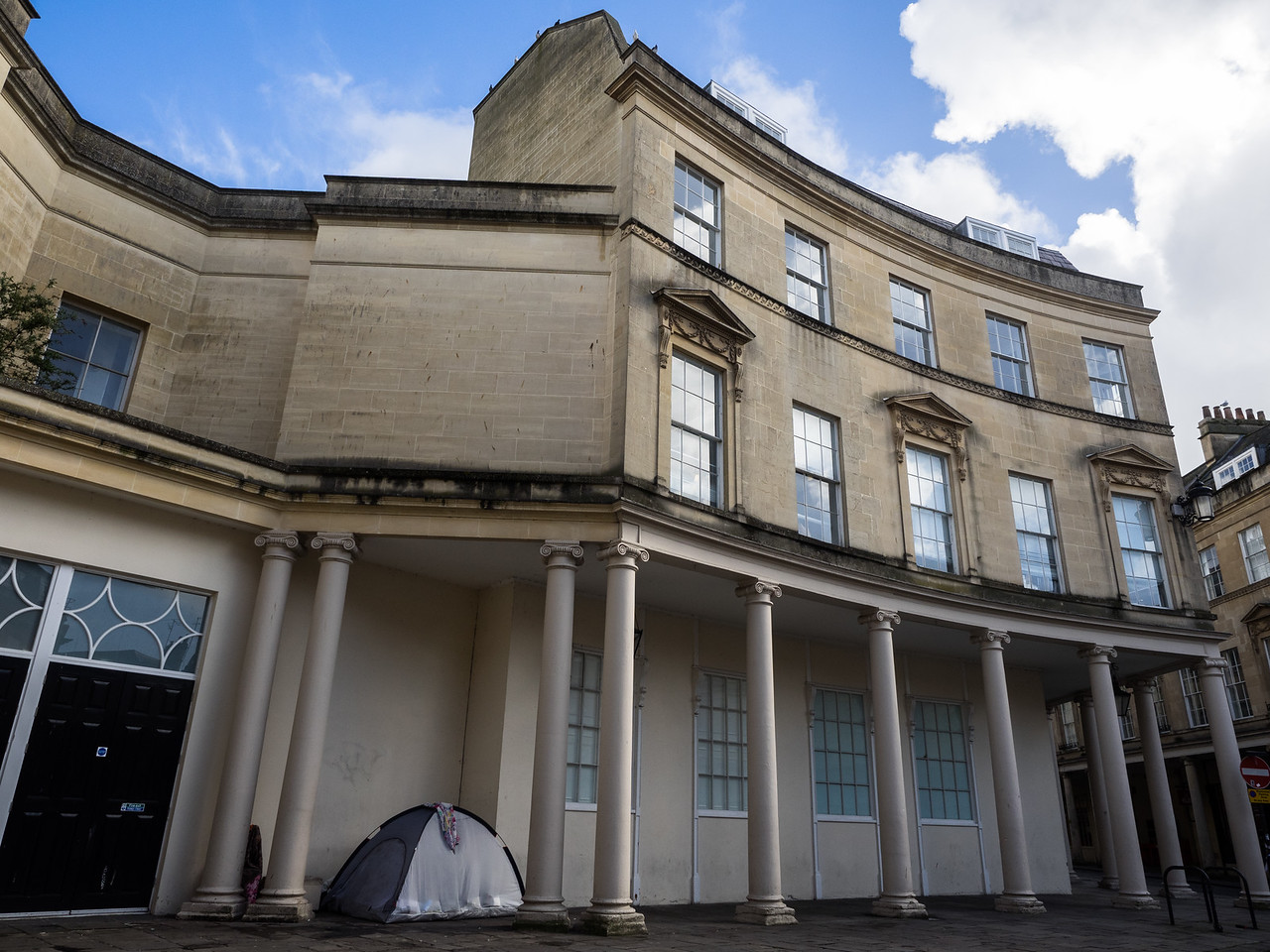 Beautiful buildings in Bath contrast with the tents of the homeless.