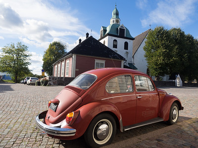 A very red car in Porvoo, with the cathedral in the background.