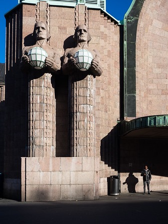 The monumental statues make for a good juxtaposition with tiny commuters standing beside them.
