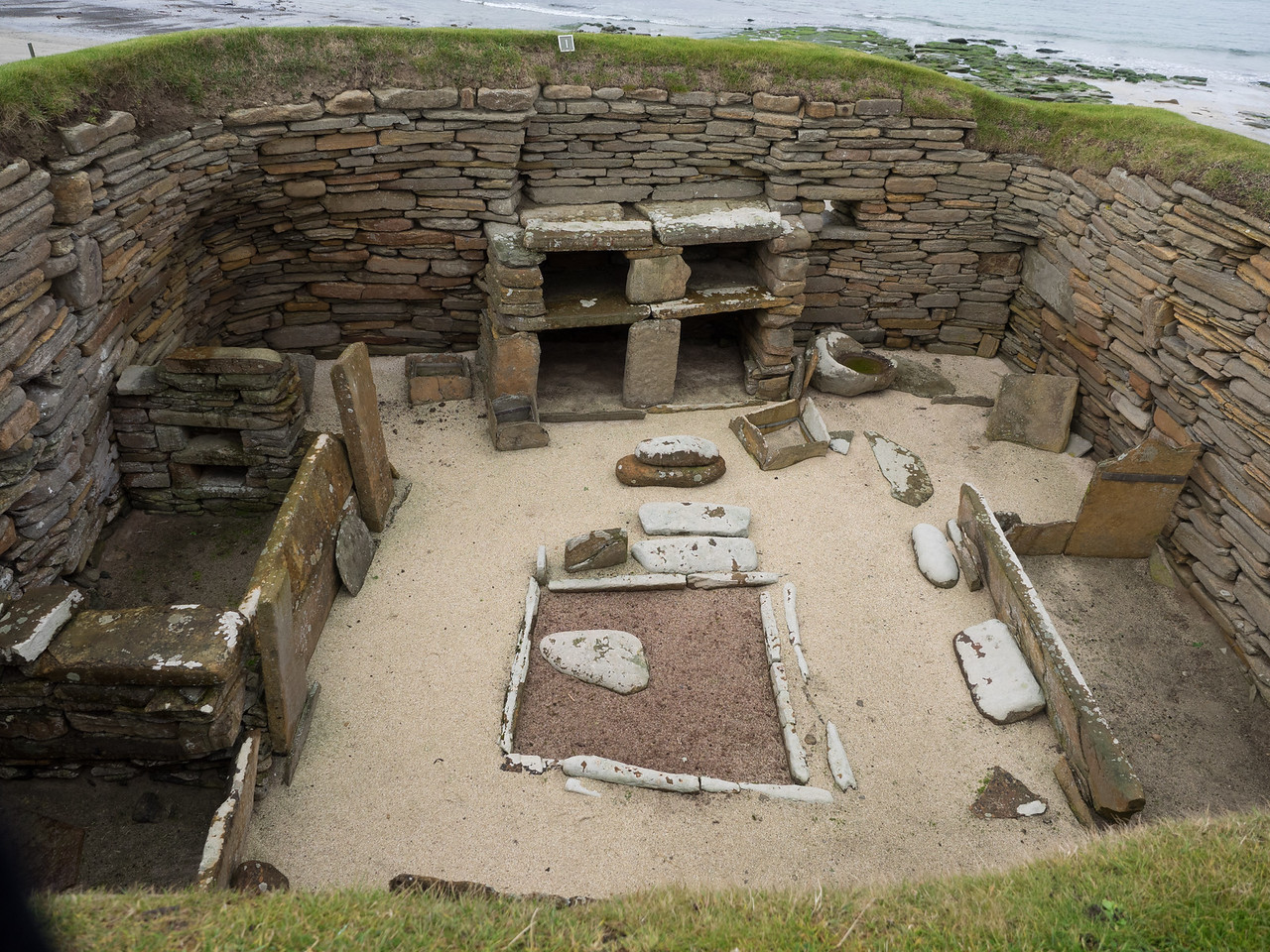 One of the Neolithic houses, complete with Flintstone-esque stone dresser. The stone setting in the middle is a hearth, and the compartments on the left were for  beds.