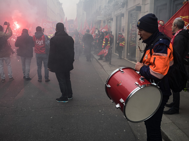 Banging the drum at some kind of trade union march. Lots of noise, light and red smoke.