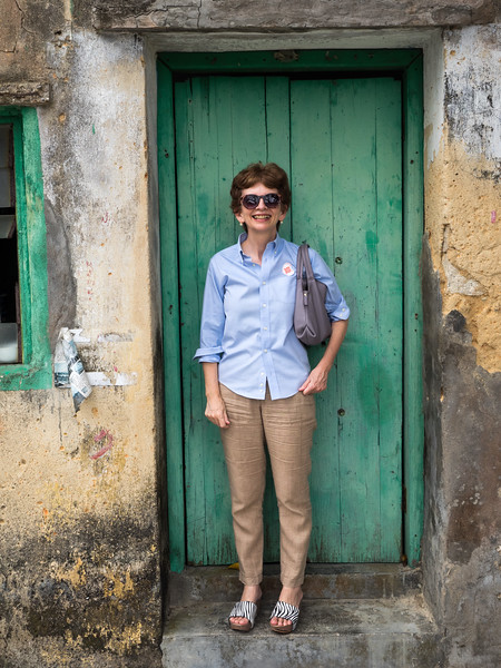 Fionnuala in sensible shoes at the door of one the old houses.
