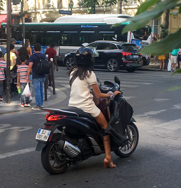 A Stylish French Woman in High Heels, Short Skirt, With a Suitcase on her Motorcycle