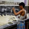 Slum bun baker, weighing his buns for consitency