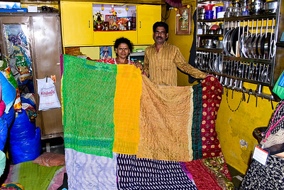 a slum couple showing us their wares, quilts from sari's, notice the orderly kitchen ware