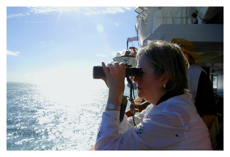 As the ship drops anchor and the passengers wait for the tenders to be lowered, I noticed this woman using her binocular surveying the group of three islands, one of which is the Devils Island. A day before, we were infomed through the ship's newsletter that the island has rough gravel roads and trail, the temperature may hit 90F and humid, there are lots of forested areas and prepare to be sweating throughout our walk. This woman who was with me in the tender, does not look like she is going for a hike. She has on a gold wrist watch, a gold bracelet, diamond ring, diamond earrings, and embroidered cotton dress. She is doing it all in style.<br /> <br /> I took this picture while directly facing the morning sun, which is still low on the horizon. I thought it will be so over exposed I will not have a record of this bejewelled lady. But the digital camera came through.