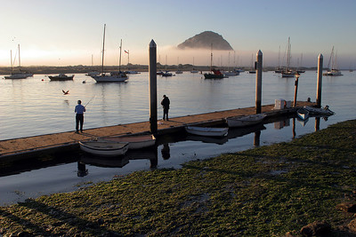 Late afternoon light settles down on Morro Bay and Morro Rock as a fog bank forms just outside the bay.