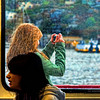 A young woman taking pictures of the city while standing at the deck of a cruise boat.