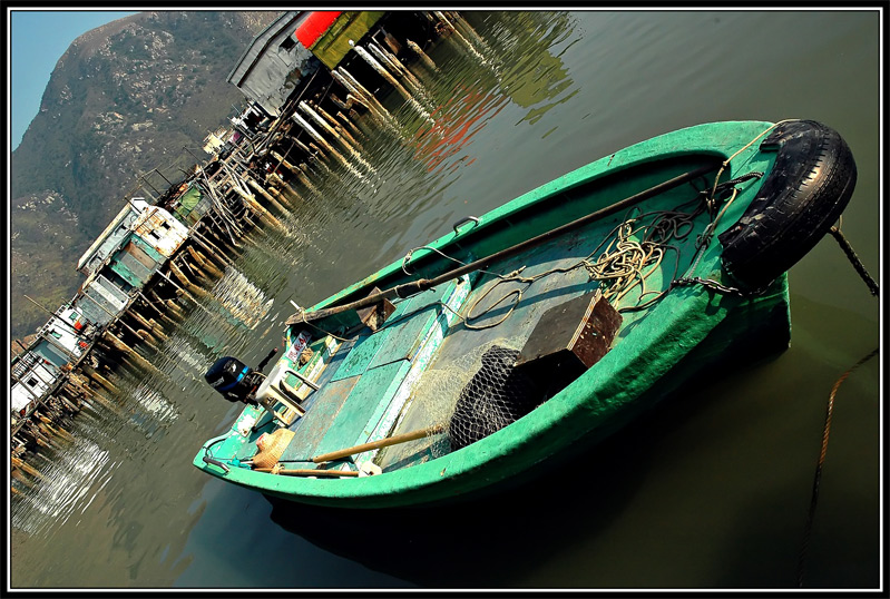 A green boat docked at Lantau Island. It looks very clean with no fishing gears. Could it be fisherman's boat? The houses on stilts are shown in the background.
