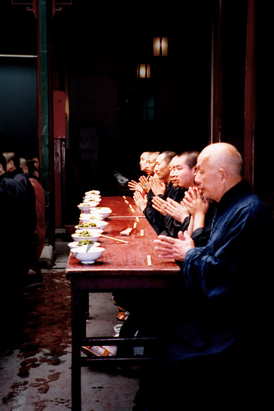 The monks having lunch of rice and vegetables.
