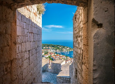 A view of beautiful Hvar harbor seen through a narrow entrance passage in the medieval stone fortress located above the town.