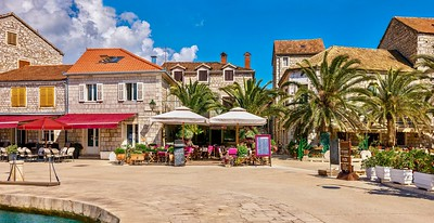 A colorful panorama of a Mediterranean resort town in summer, with restaurants and cafes along the waterfront promenade.