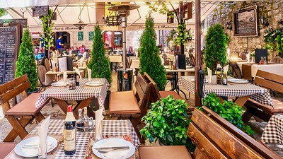 An attractive outdoor restaurant catering to tourists is set up for the lunch crowd.