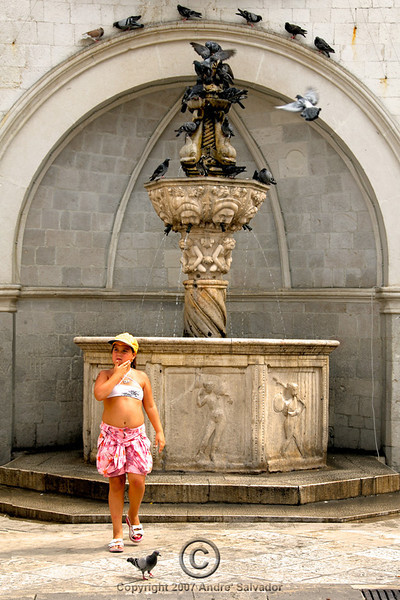 This young tourist keeps wiping herself with cool water from the fountain.