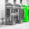 Five London Telephone boxes all in a row in black and white - one Green
